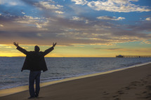 man with raised hands on a beach