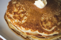 butter on a stack of pancakes