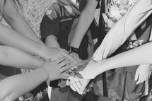 children with hands stacked on top of each other