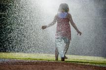 Girl playing and splahing in water sprinklers.