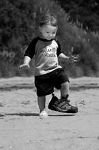 Toddler wearing dad's shoe