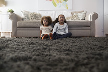 sisters sitting on a rug in a living room