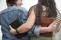 young women hugging holding Bibles