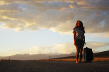 a young woman standing in the middle of a road with a suitcase at sunset