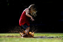Child splashing in a mud puddle.