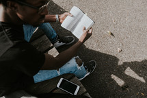 man sitting on a picnic table reading a Bible