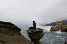 a woman sitting on a rock peak