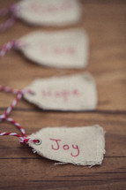 "Christmas gift tags lined up on a wooden table, the first one reading, ""Joy."""