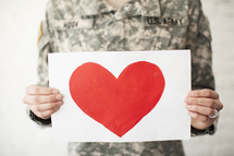 Red heart on a white sheet of paper being held by an army soldier.