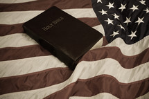 Holy Bible on waving American flag with retro look.