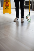 a man with a dust mop and a wet floor sign