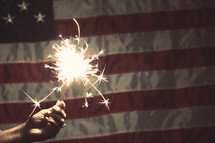 sparkler in front of an American Flag