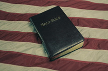 Holy Bible on American flag with retro effect.