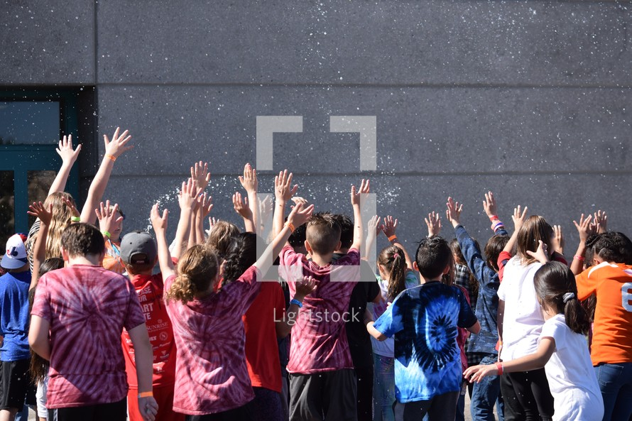 group of children with hands raised being splashed with water