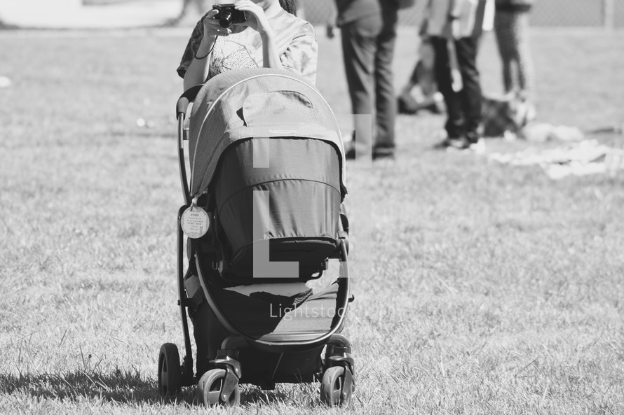 a mother pushing a stroller in the grass and taking a picture with a camera