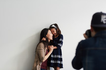 photographer taking a picture of a mother and daughter in studio