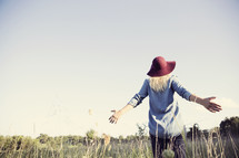 woman in a hat standing in a field with open arms