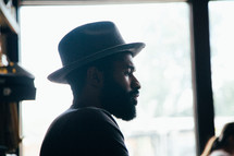 side profile of a man with a thick beard and hat