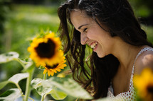 A smiling young woman in a field of sunflowers.