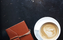 coffee cup and leather bound journal