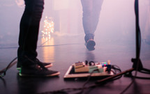 guitar pedals on stage at a concert