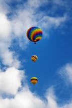 3 colorful hot air balloons ascending into the blue sky