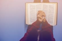 praying hands over an open Bible