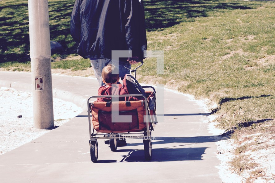 a father pulling his kids in a wagon