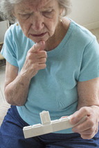 elderly woman looking at her pill box