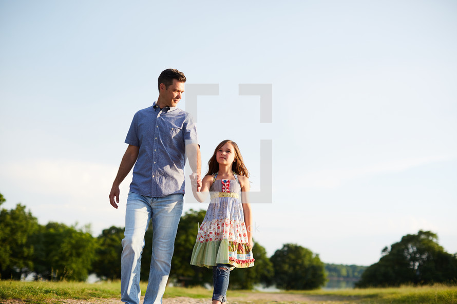 a father walking outdoors with his daughter