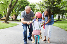 grandparents helping a young girl learn to ride a bike