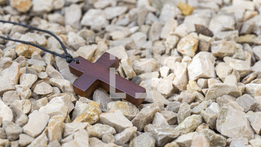 wooden cross necklace in gravel