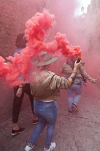 friends walking in an alley with colored smoke flares