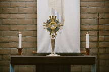 Table with a monstrance and candles in front of a brick wall.