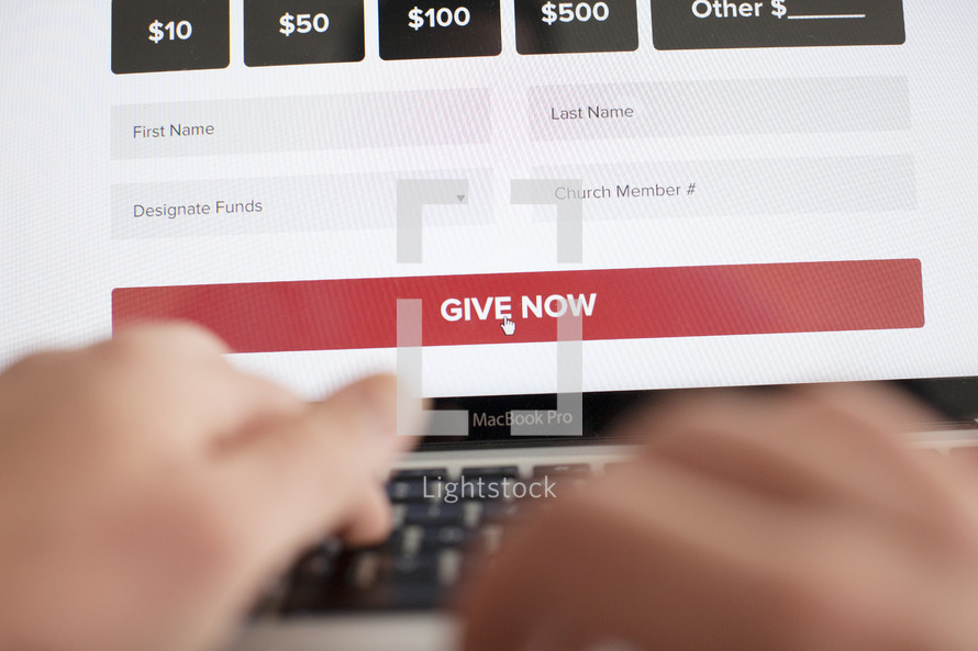 closeup of man donating to a charity or tithing to a church online and getting ready to click the give now button.