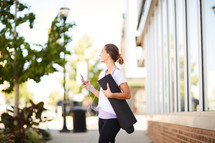 a woman carrying a yoga mat and listening to iPhone