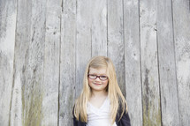 A little girl with glasses and blonde hair stands against a wooden fence.