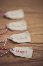 "Christmas gift tags lined up on a wood grain background, with the word ""Hope"" on the first one in line."