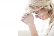 woman alone with head bowed and praying hands