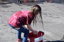 a child wetting a sponge in a bucket for a car wash