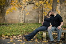 pregnant woman kissing a man sitting on a park bench