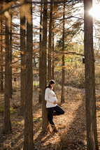 woman leaning against a tree with her hands on her pregnant belly