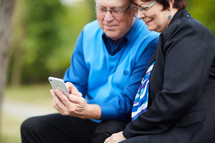 elderly couple sitting on a park bench looking at a cellphone