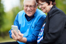 elderly couple sitting on a park bench looking at a cellphone screen