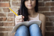 A young woman writing in a journal.