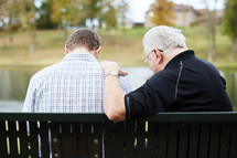 elderly man praying with and talking to a young man