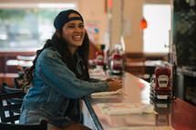 A laughing young woman sitting at a diner counter.