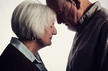 elderly man and woman with head bowed in prayer