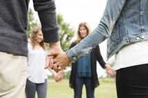 family holding hands in a circle in prayer