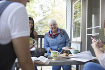 Smiling women having a Bible study at a patio table.